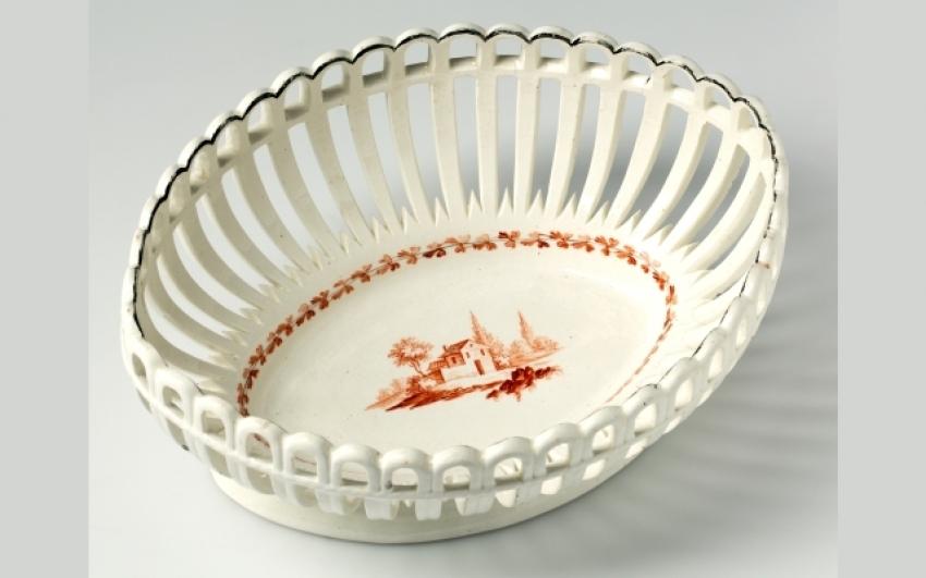 Prořezávaná oválná miska bíle polévaná, ve středu misky je namalovaná romantická krajina s domem, okolo roku 1820